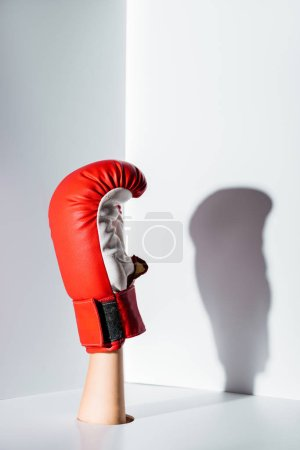 cropped image of woman showing hand in red boxing glove through hole on white