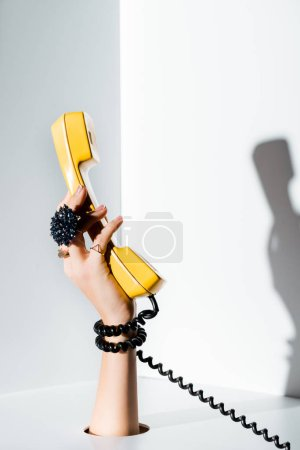 cropped image of girl holding yellow handset of retro telephone in hand through hole on white
