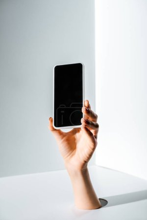 cropped image of woman holding smartphone with blank screen in hand through hole on white