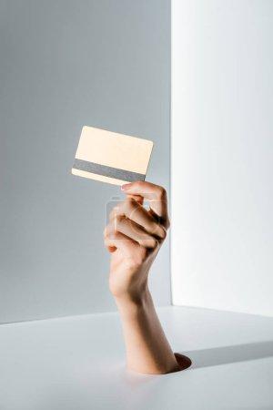 Foto de Imagen recortada de la mujer que sostiene en la mano tarjeta de crédito a través del agujero en blanco - Imagen libre de derechos