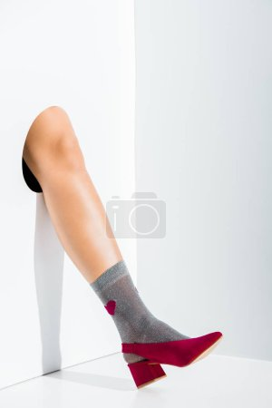cropped image of girl showing leg in grey sock with heart and burgundy high heel in hole on white