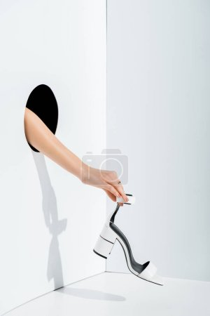 Photo for Cropped image of girl holding white high heel in hand through hole on white - Royalty Free Image