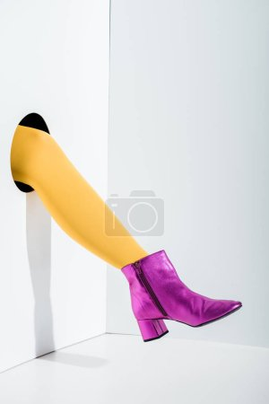 cropped image of woman showing leg in bright yellow tights and ultra violet shoe in hole on white