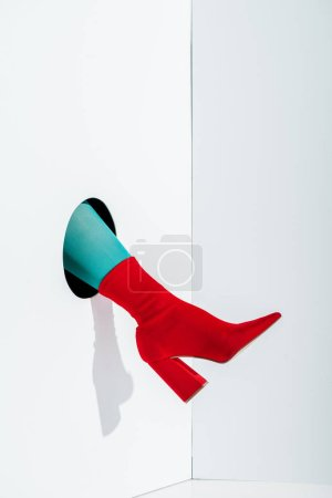 cropped image of girl showing leg in bright turquoise tights and red shoe in hole on white