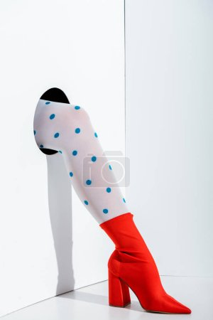 cropped image of girl showing leg in trendy white tights with blue dots and red shoe in hole on white