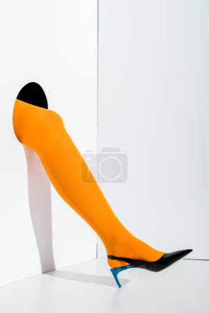 cropped image of girl showing leg in stylish orange tights and black high heel in hole on white