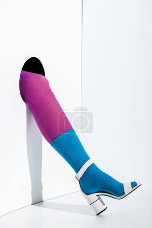 cropped image of woman showing leg in violet tights, blue sock and white high heel in hole on white