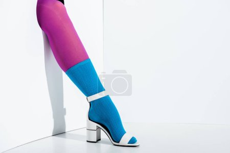 cropped image of girl showing leg in fashionable violet tights, blue sock and white high heel in hole on white