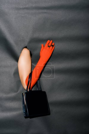 Photo for Cropped image of girl showing hand in fashionable orange glove and black handbag through black paper - Royalty Free Image