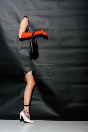 Photo for Cropped image of girl showing hand in orange glove and black handbag, leg in white high heel through black paper - Royalty Free Image