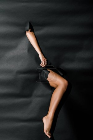 Photo for Cropped image of girl showing through black paper - Royalty Free Image