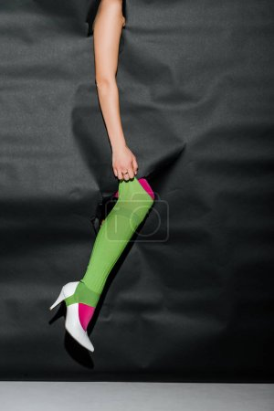 cropped image of girl showing leg in pink tights and white high heel through black paper, holding green gaiter