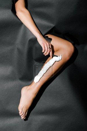Photo pour Image recadrée de jambe fille raser rasoir à travers des trous dans le papier noir - image libre de droit