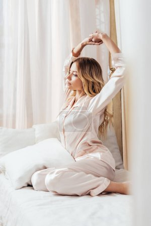girl in pajama stretching with raised arms in bed during morning time at home