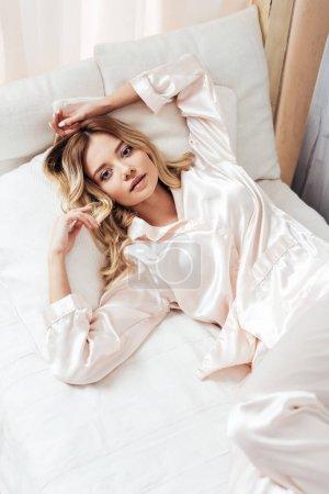 Photo pour Vue d'angle élevé de fille en pyjama au repos au lit pendant une heure du matin à la maison - image libre de droit