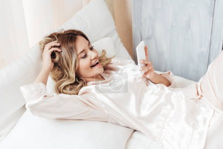 Photo for Happy girl using smartphone in bed during morning time at home - Royalty Free Image