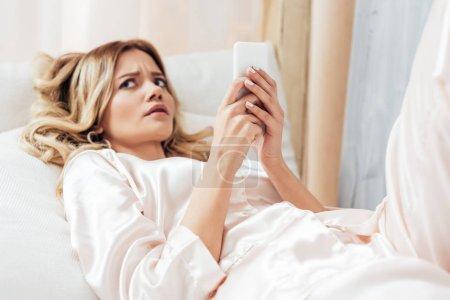 Photo pour Irrité de jeune femme à l'aide de smartphone dans son lit pendant une heure du matin à la maison - image libre de droit
