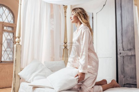 Photo for Happy blonde girl in pajama having fun with pillow in bed at home - Royalty Free Image