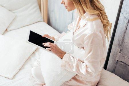 Photo pour Vue partielle de la femme blonde à l'aide d'une tablette numérique avec écran blanc au lit le matin à la maison - image libre de droit