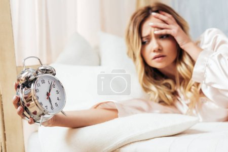 selective focus of irritated young woman turning off alarm clock in bed at home