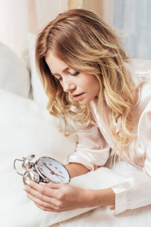 attractive blonde young woman turning off alarm clock in bed at home