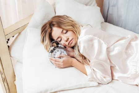 Photo for Beautiful blonde young woman sleeping with alarm clock in bed at home - Royalty Free Image