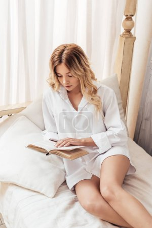 Photo for Pretty girl reading book in bed during morning time at home - Royalty Free Image