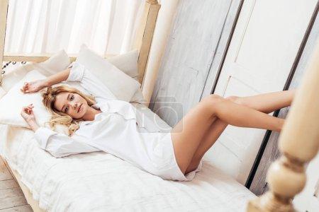 Foto de Atractiva mujer joven rubia mirando a cámara en la cama en casa - Imagen libre de derechos