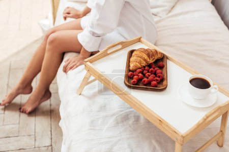 cropped shot of woman sitting on bed with breakfast on tray at home