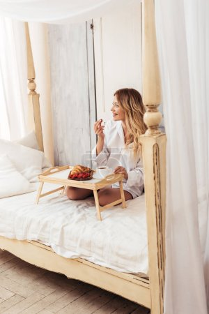 joyful woman having breakfast with coffee, croissant and raspberries in bed at home