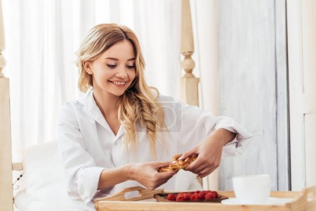 happy woman tearing up croissant in bed with breakfast on tray during morning time at home