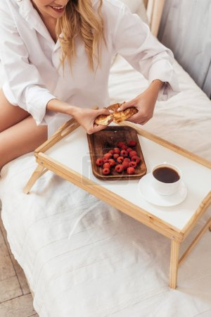partial view of woman tearing up croissant in bed with breakfast on tray during morning time at home