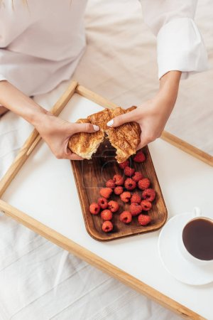 cropped image of woman tearing up croissant in bed with breakfast on tray during morning time at home