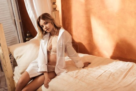 beautiful female model in beige lace lingerie and white shirt posing on bed