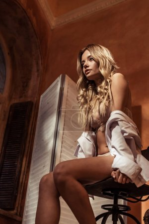low angle view of young blonde female model in white shirt and lace lingerie posing on chair