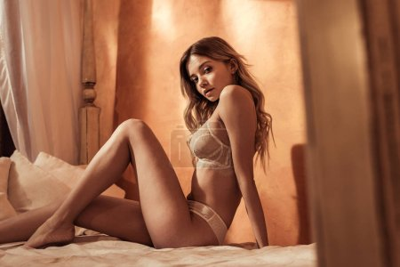 Photo for Gorgeous blonde girl wearing seductive lace underwear and posing in bed - Royalty Free Image