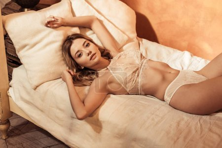 Photo for Blonde girl wearing seductive lace lingerie and posing in bed - Royalty Free Image