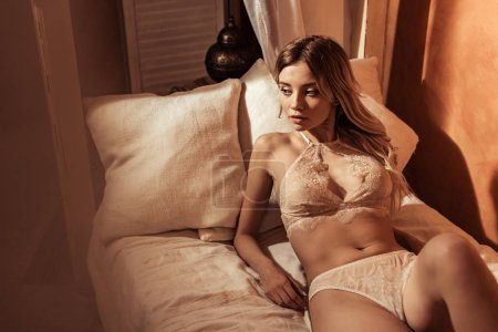 Photo for Selective focus of female model wearing sexy beige lingerie and posing in bed - Royalty Free Image
