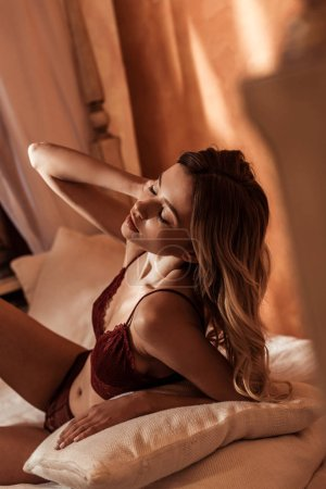 young female model in seductive red lingerie posing on bed