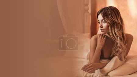 Photo for Selective focus of female model in red lingerie posing on bed - Royalty Free Image