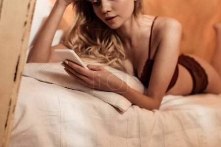 selective focus of blonde girl in red lace lingerie using smartphone while laying on bed