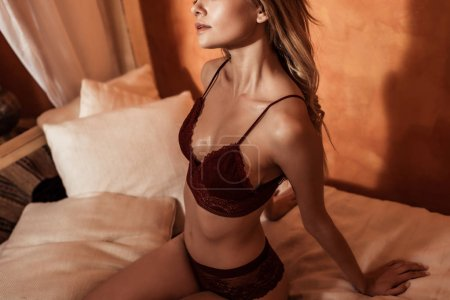 partial view of female model in red lace lingerie posing on bed