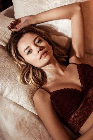 Photo pour Superbe femme blonde qui pose en lingerie rouge et en regardant la caméra dans son lit - image libre de droit