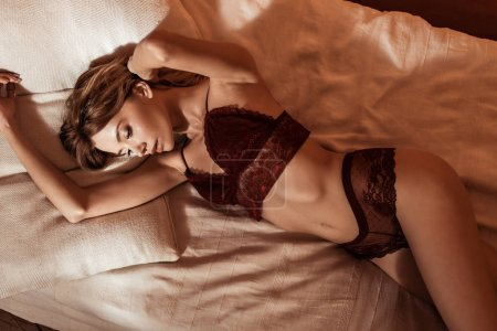 female model wearing red lace lingerie and laying in bed