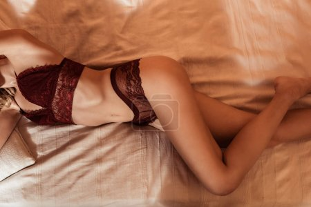 Photo for Partial view of seductive girl wearing red lace lingerie and laying in bed - Royalty Free Image