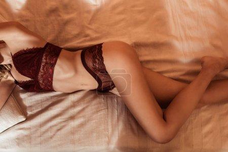 Photo pour Vue partielle de séduisante fille portant de la lingerie en dentelle rouge et couchée au lit - image libre de droit