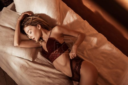 high angle view of beautiful young woman wearing red lace lingerie and laying in bed