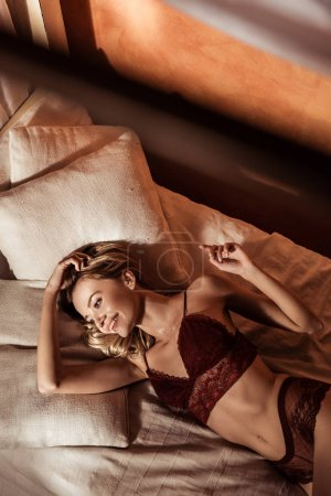 high angle view of happy beautiful young woman wearing red lace lingerie and laying in bed