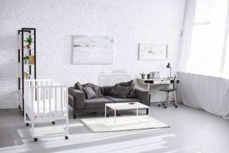 modern interior of living room with baby crib, sofa and workplace