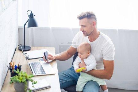 Foto de Padre guapo sentado en el escritorio de la computadora con tarjeta de crédito para compras en línea y manteniendo la hija en casa - Imagen libre de derechos
